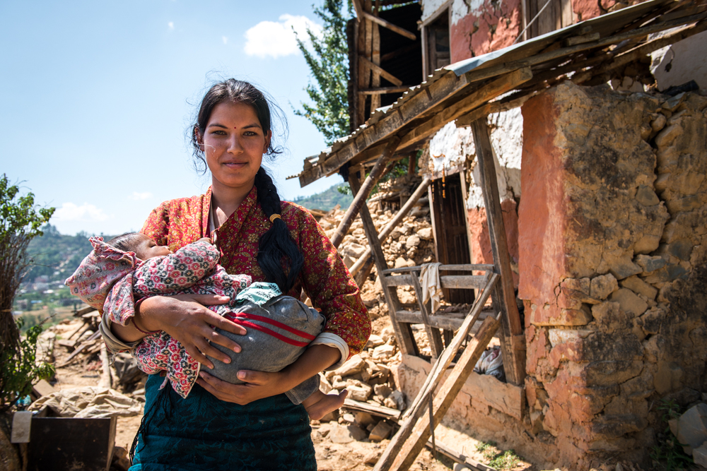 In ramkot, a mother stands in front of her broken home with her 3 month old baby.