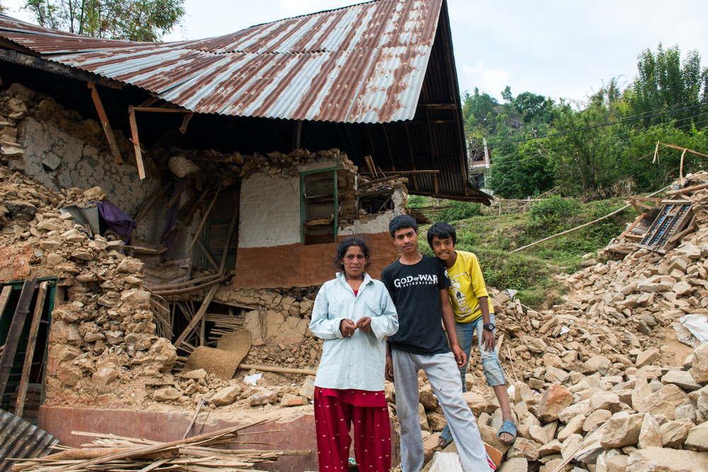 A family stands in front of the remains of their house. Unfortunately in Nepal there are very few construction standards, most of the houses built with brick alone crumbled quickly.