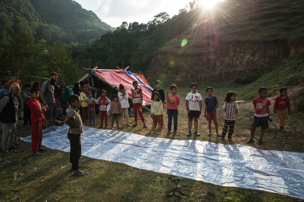 Families of Goldhunga gather around to watch as we unravel and asses a giant tarp.