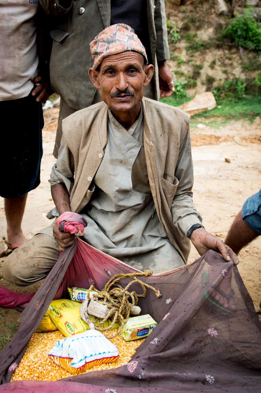 A man receives some rope, oil, lentils, rice and soap in Sindhupalchok.