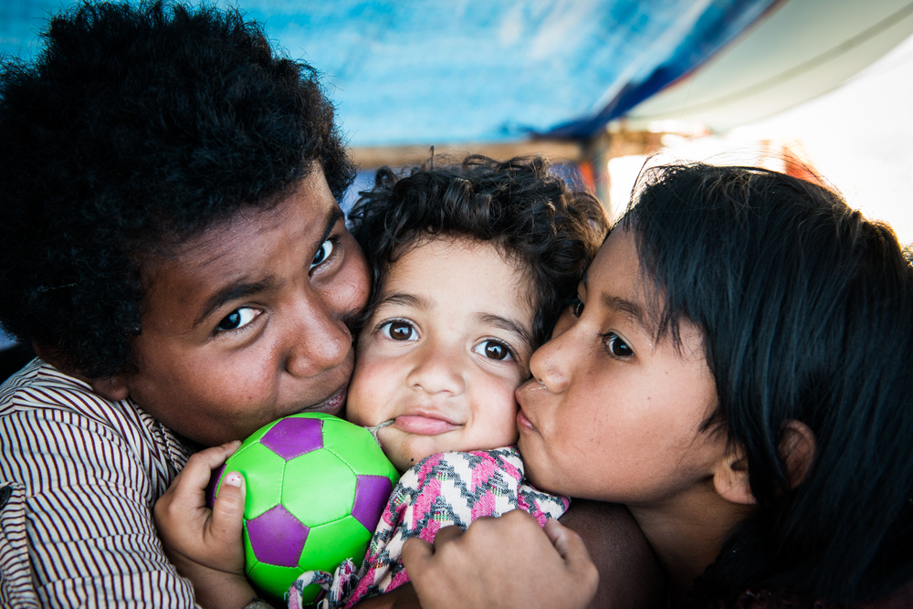 Children at an orphanage provide comfort for the young girl in the middle.