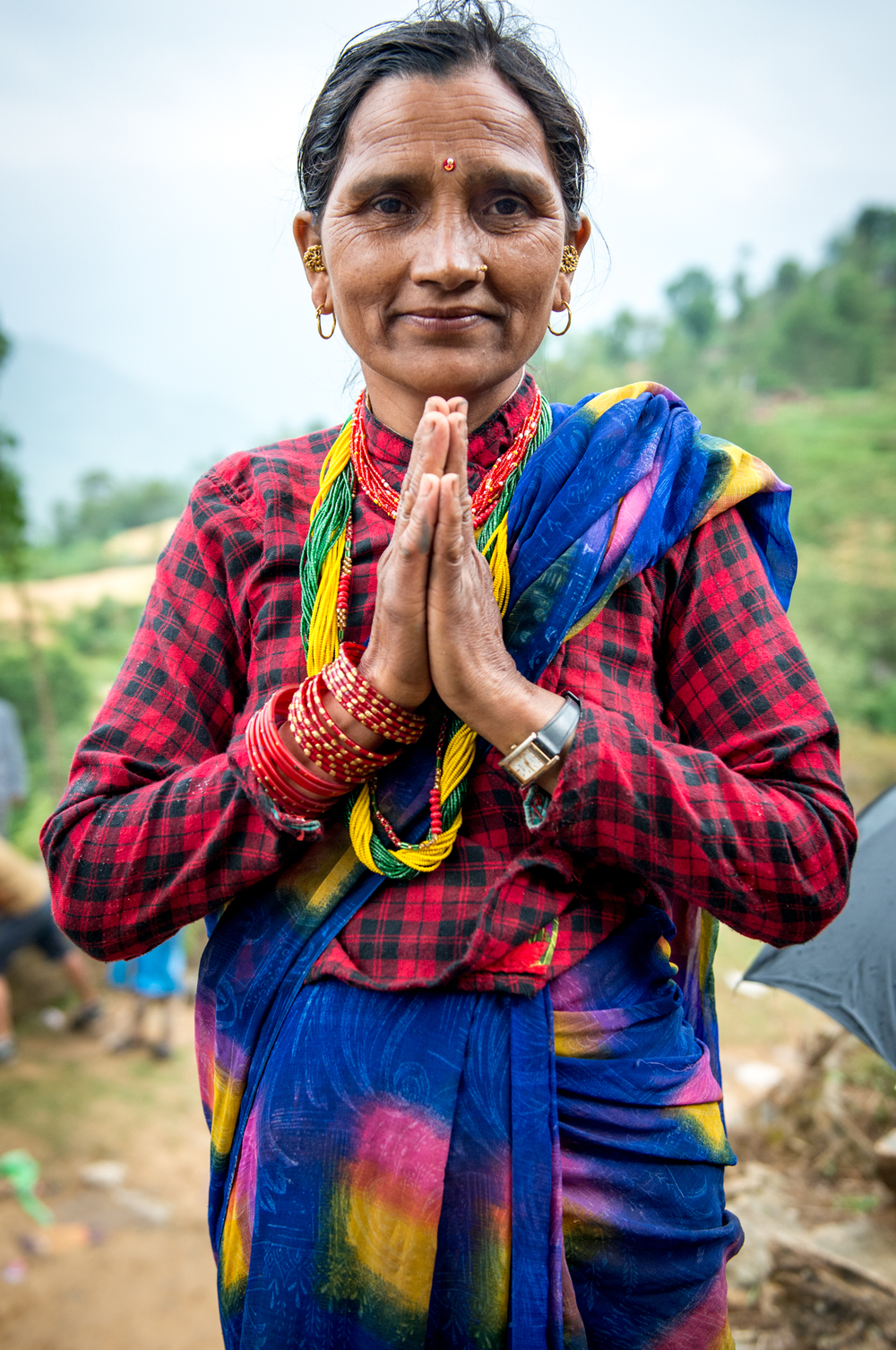 A woman greets with 'Namaste' as she receives our supplies.