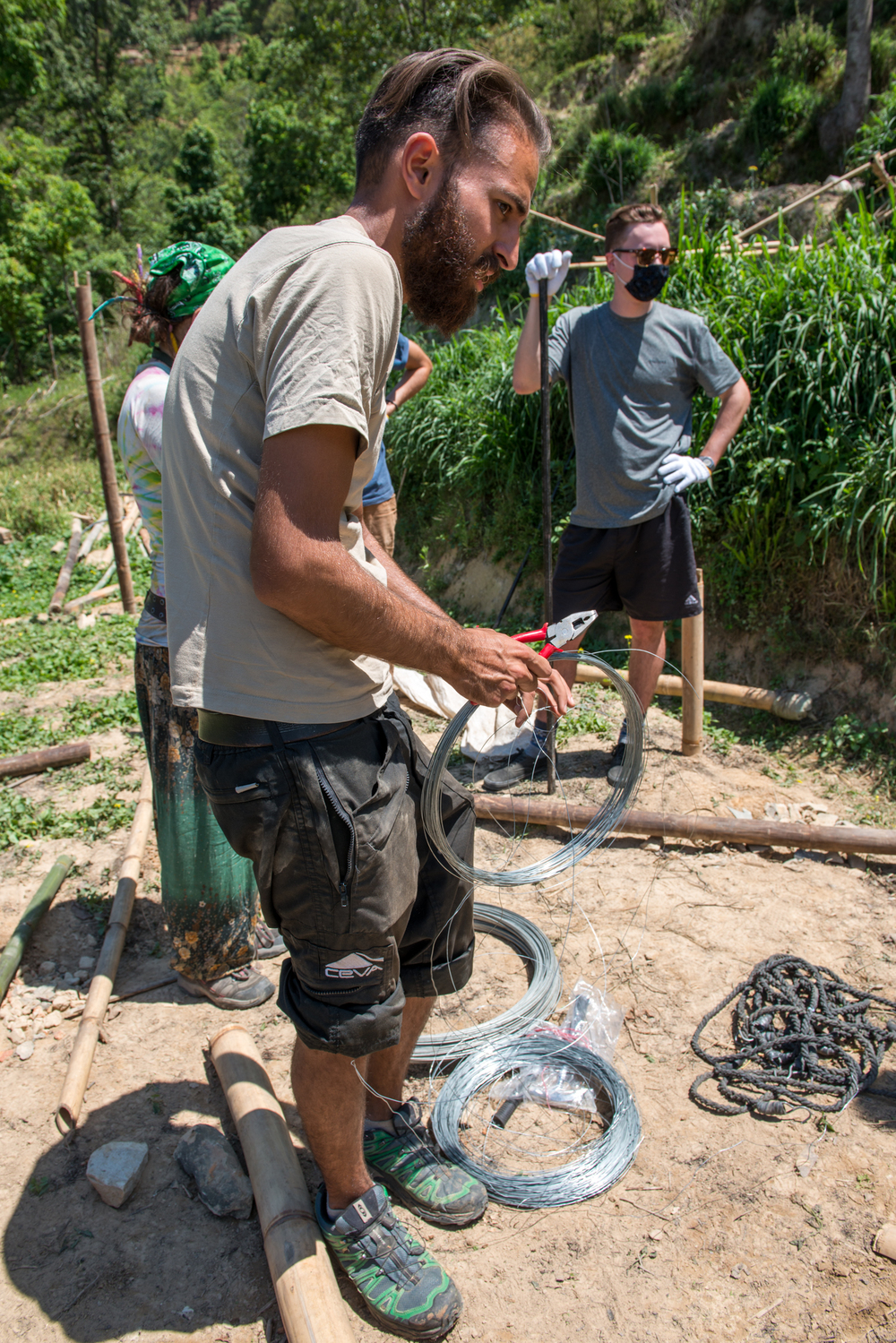 James organizes the wires used for building the bamboo shelters.