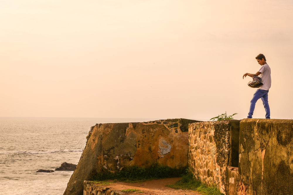 A motorcyclist takes a moment to watch the sunset - Galle City, Sri Lanka.