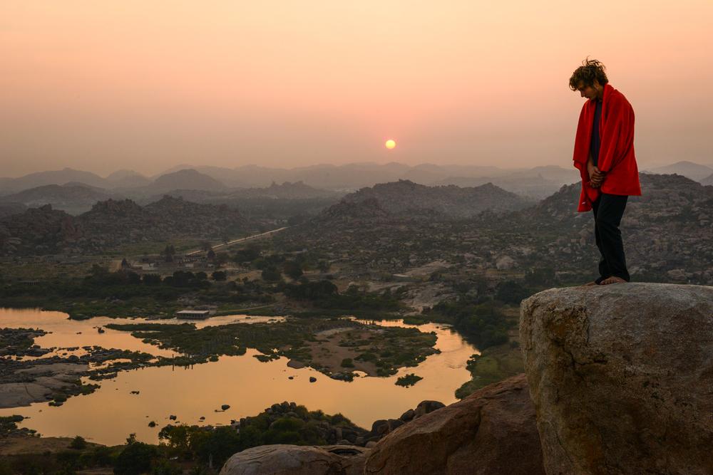 A climber enjoys the sunrise - Hampi India.