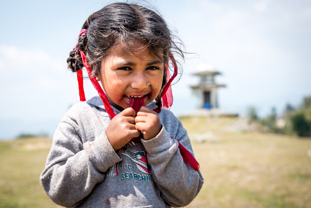 A small girl shows off her hair ribbons. Most of the nepalese girls in the area wear these ribbons as a requirement for school -Sarangkot, Nepal.