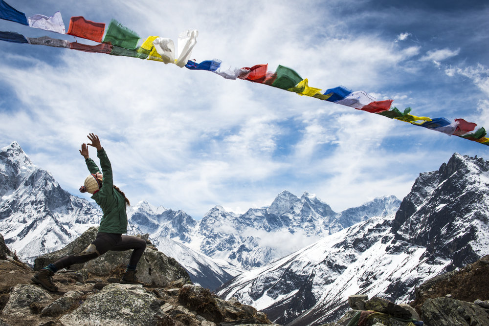 A hiker strikes a yoga pose en route to Everest Basecamp.