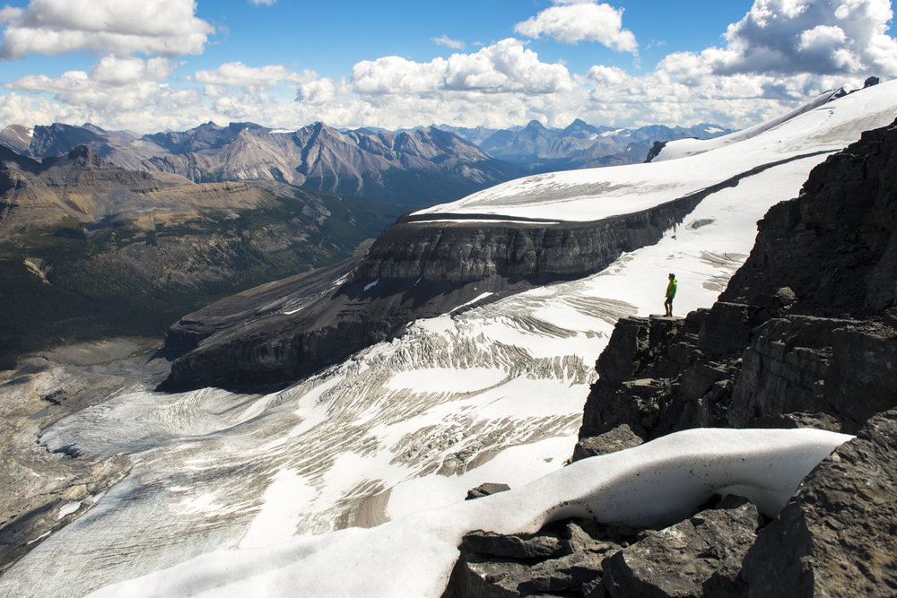A hiker is rewarded with magnificent views of surounding glaciers on Little Hector Peak.