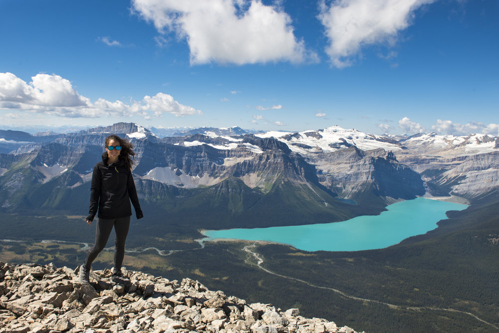 A hiker poses in front of Hector Lake.