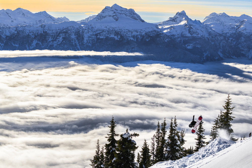A snowboarder enjoys beautiful inversions in the back country of Revelstoke mountain resort.