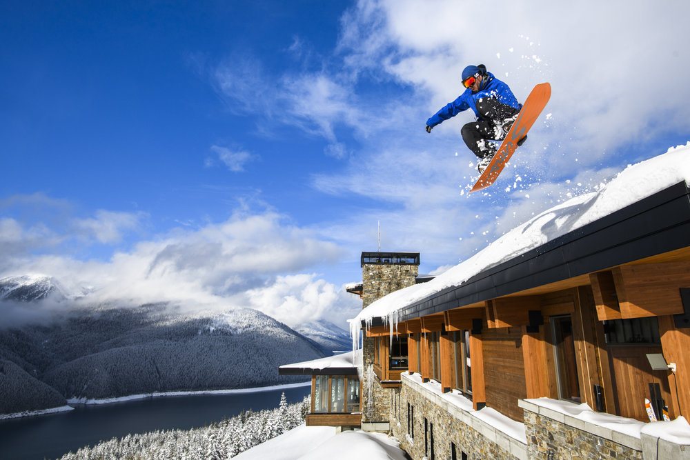 A snowboarder holds a grab as he launches off of Mica Heli Lodge.