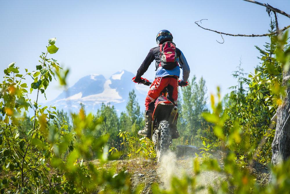 A dirt biker enjoys scenic views in revelstoke, British Columbia