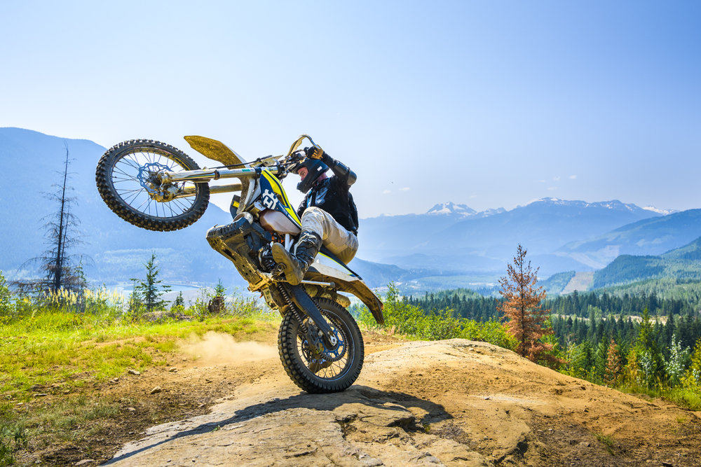 A dirt biker throws a wheelie on local Revelstoke trails in British Columbia.
