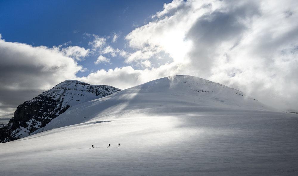 Three friends ski tour above the Athabasca Glacier towards Snow Dome