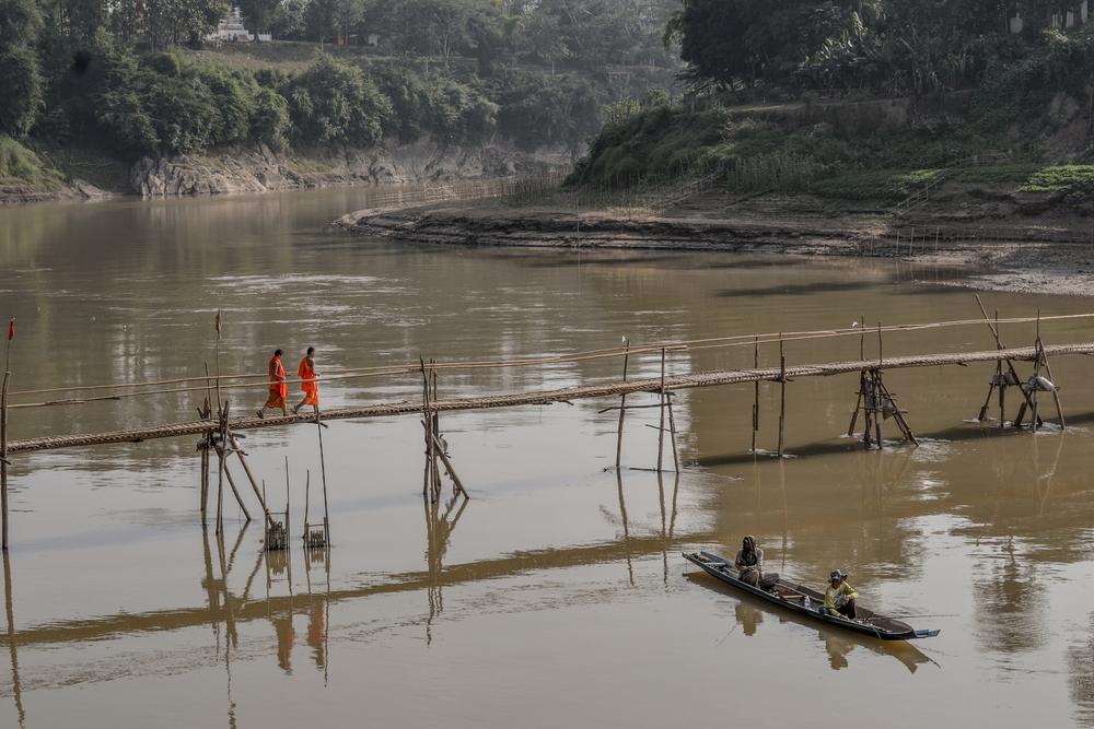 Novice monks crossing the Nam Khan River. Luang Prabang, Laos
