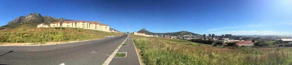 Panorama of the De Waal Drive residencies beneath Devil's Peak, with the expanse of fallow land sprouting foods and home to many who live amongst the grasses.  Lion's Head and Signal Hill to the distance and the CBD and harbour to sea at the very end.