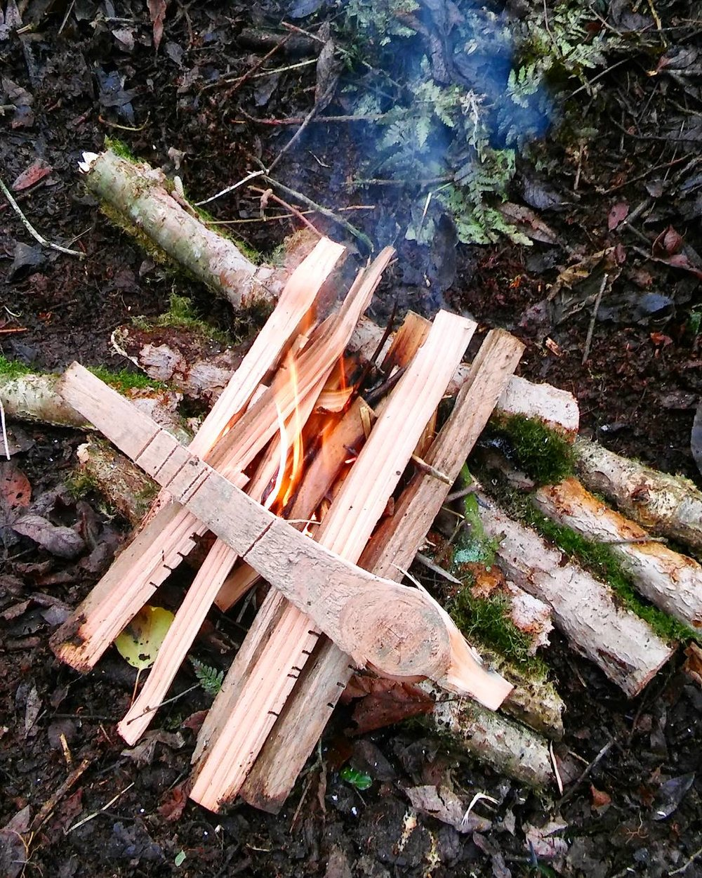 Step 2: Create a bed of mini logs for the fire to sit on, if the ground is really damp. Lay your tinder across the fire with one side slightly raised to assist with airflow.