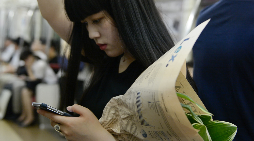 Japanese girl holding flowers in the subway.