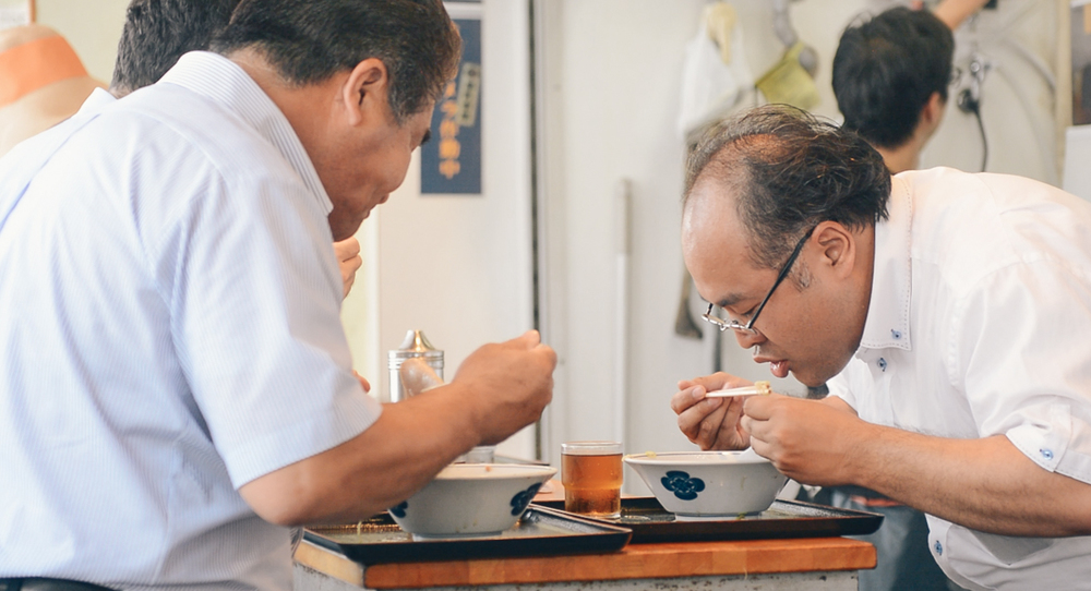 Two men eating Ramen nearby Tsukiji Market.