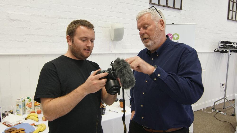James explaining camera settings to john