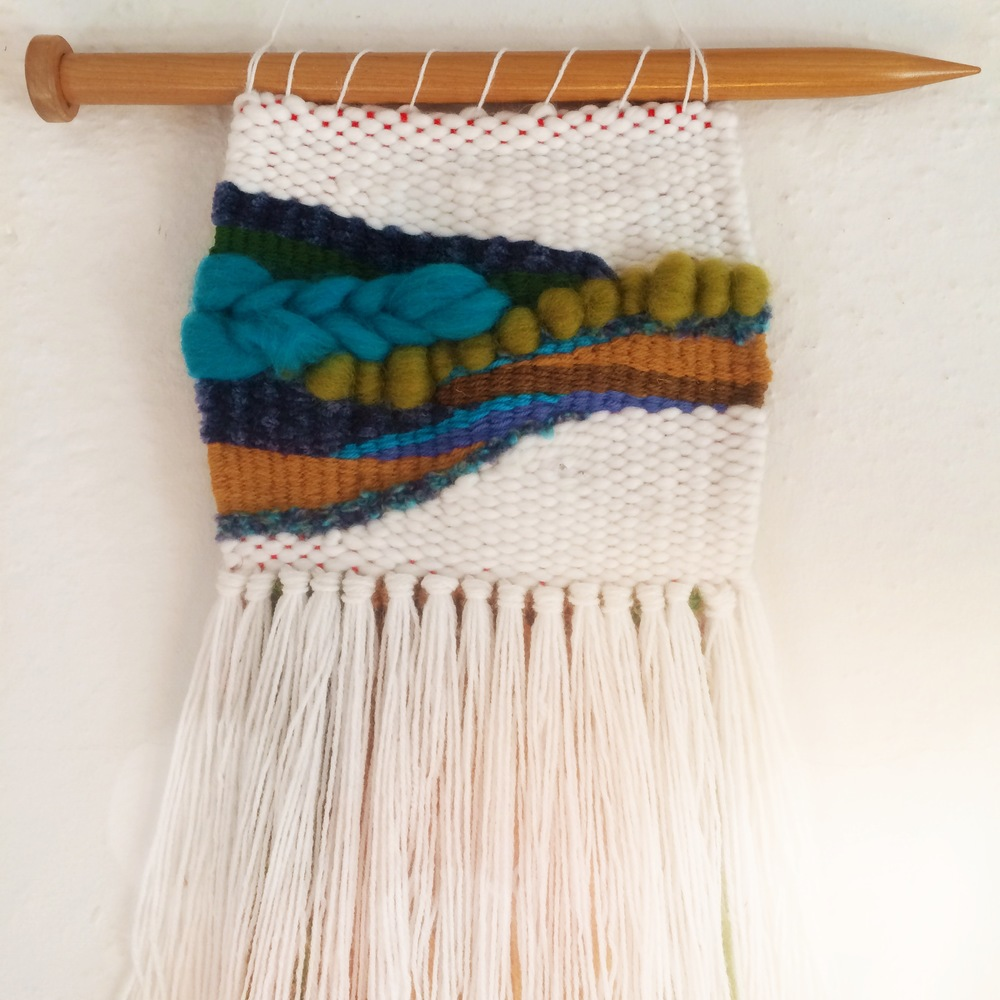 Cool colors hung on a large wooden knitting needle.