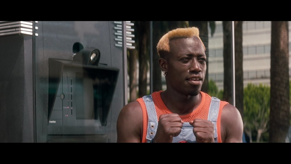 Wesley Snipes in Demolition man, wearing blocked out blue with a fishnet top used to accent and compliment the outfit. Reminscent of Ghesquière's denim blue jump suit and fishnet pieces.