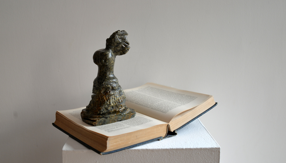 "Broken Angel, soapstone and found Dictionary of the Bible, 9"" x 9"" x 8.5"", 2014"