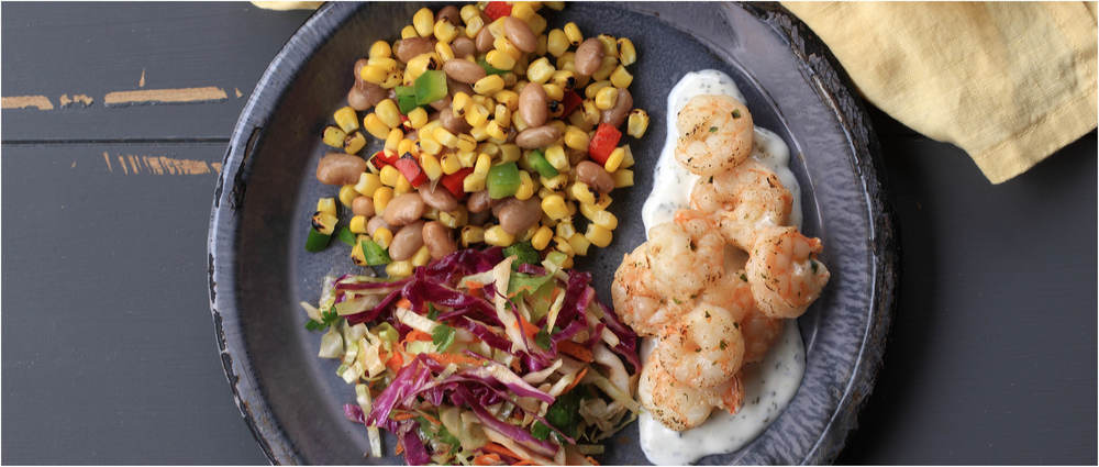 Cilantro lime shrimp with Mexican crema, pinto beans, fire roasted corn and peppers, and Mexican cabbage slaw from Good Measure Meals.