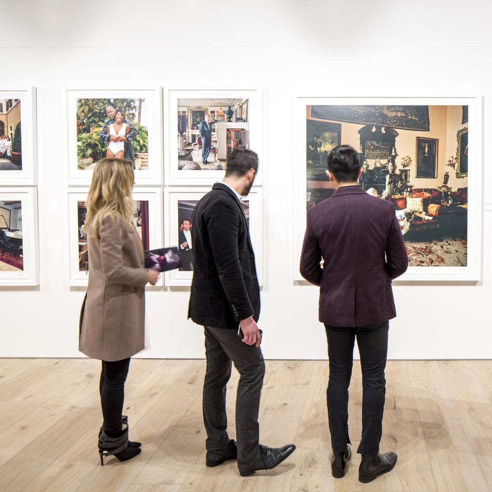 Guests looking at work displayed during opening night of the exhibition.