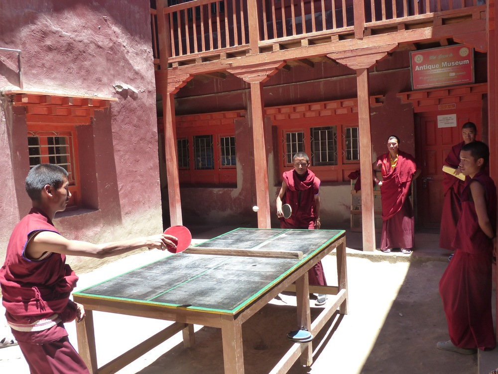 Local monks play ping-pong in the monastery courtyard