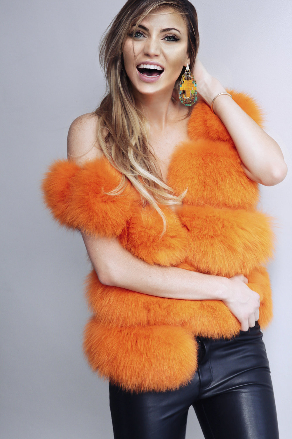 UK fashion influencer is a wearing a orange Lola Belle Fur gilet www.lolabellelondon.com (2)