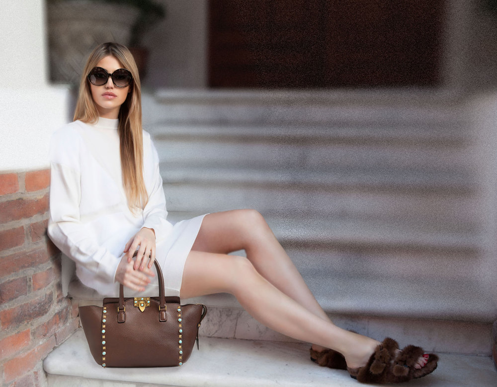 Fashion Influencer is wearing a white wool and cashmere knee length dress with brown mink fur birkenstock with a camel stud valentino hand bag. Retro Sunglasses by Chanel. (3)