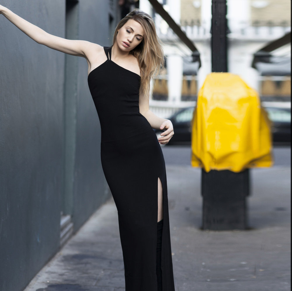 Maureen is photographed in the streets of london, with a black side shoulder strap full length dress with a slit from @nakdfashion