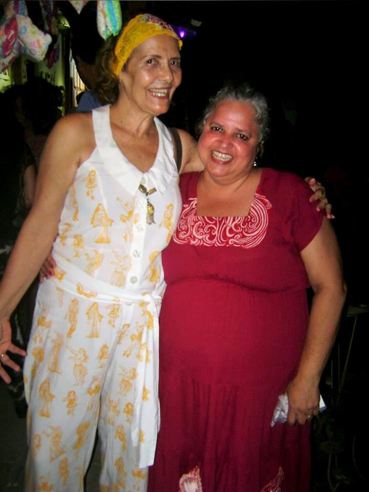Duas amigas de Regina. Uma delas está vestindo um macaquinho com as estampas das figuras dançantes da artista
