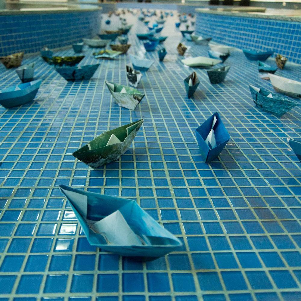 Instalação com barquinhos de papel no espelho d'água da galeria
