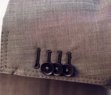 The surgeon cuff signals that the suit is bespoke. The one button undone is a subtle way of showing you have a custom made suit.  If you want to take it back further, this style element gets its name from days when there were more physicians on the now iconic Savile Row than tailors.  Once the suit makers moved in, they catered to their clientele by designing jacket and making jackets with functional sleeve buttons that could be unfastened and rolled back like shirt sleeves.  This feature gave the Doctor the ability to work on a patient without removing his jacket, which is in stark contrast to the purely decorative and non-functional buttons that are attached to most suit jacket or blazer sleeves