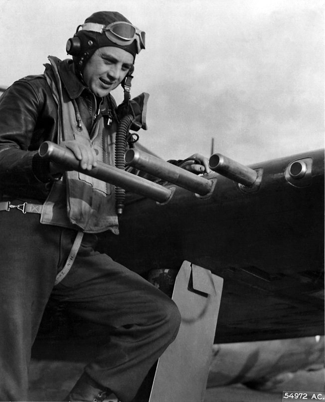 Examining the .50 caliber machine guns on his P-47C Thunderbolt.