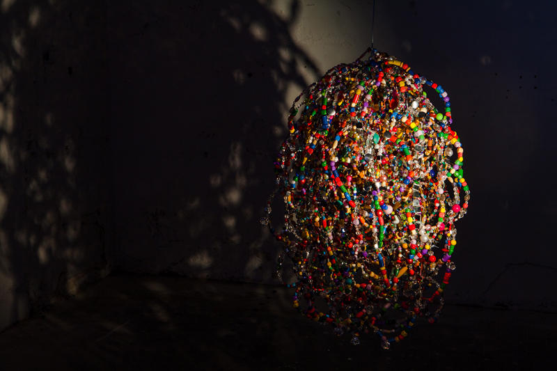 Tumour  (2012), beads, mirror mosaic, wire, bubble wrap, tape, engine. Mirror mosaic on plywood. Electric light. Variable size.