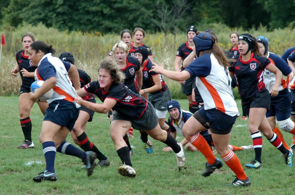 Leenie taking down her opponent in a Rugby match.