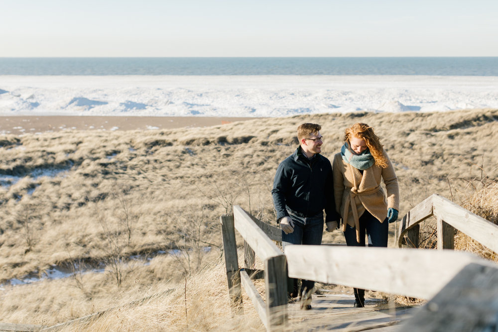 A couple walking along the beach during their engagement photography session in the Midwest.