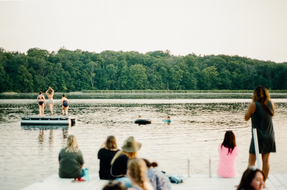 A photo of women jumping into the lake during Let's Camp 2018 at Camp Wandawega in Elkhorn, Wisconsin.
