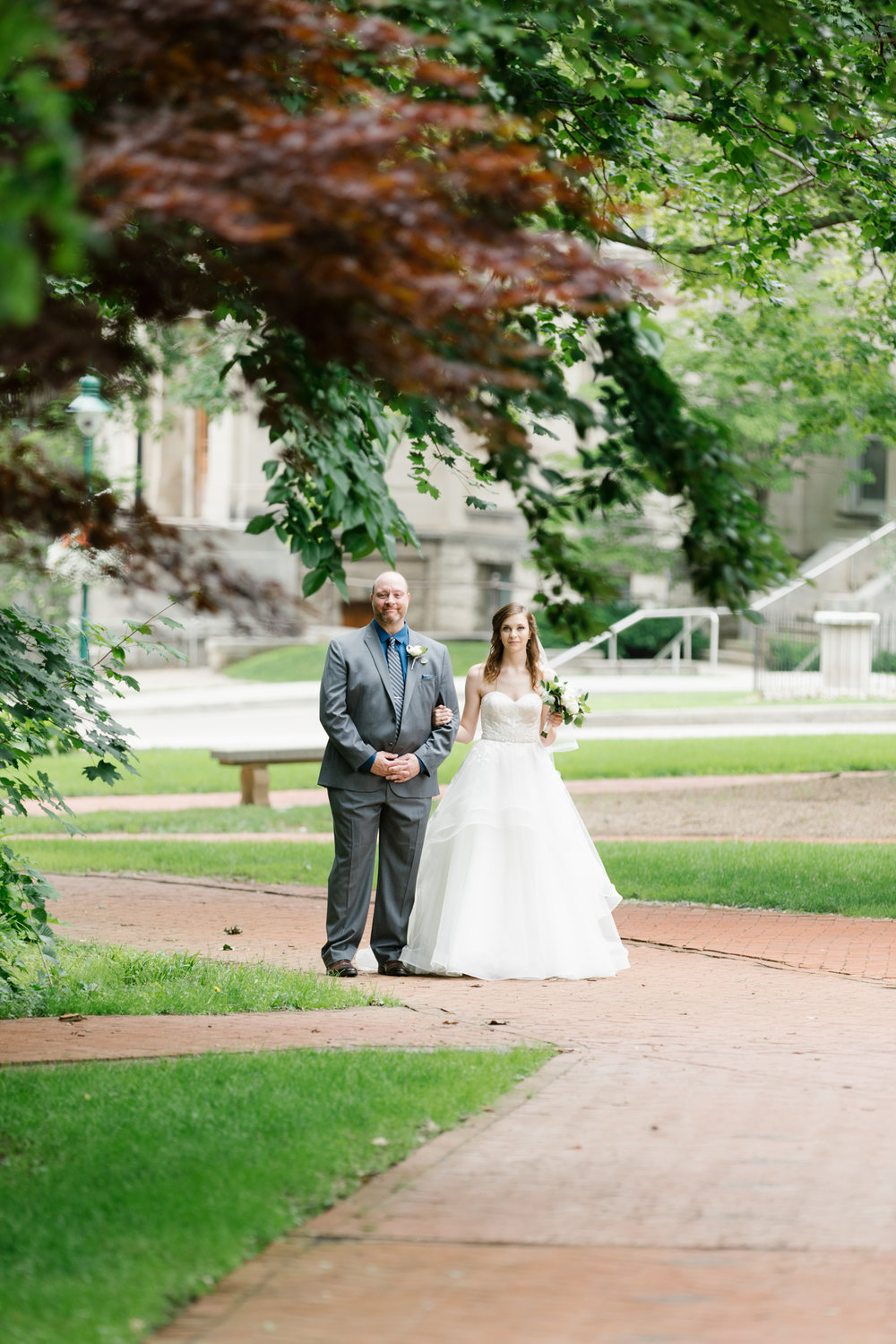 A photo of a bride walking down the aisle during her wedding at the Indiana Memorial Union at Indiana University in Bloomington, Indiana.