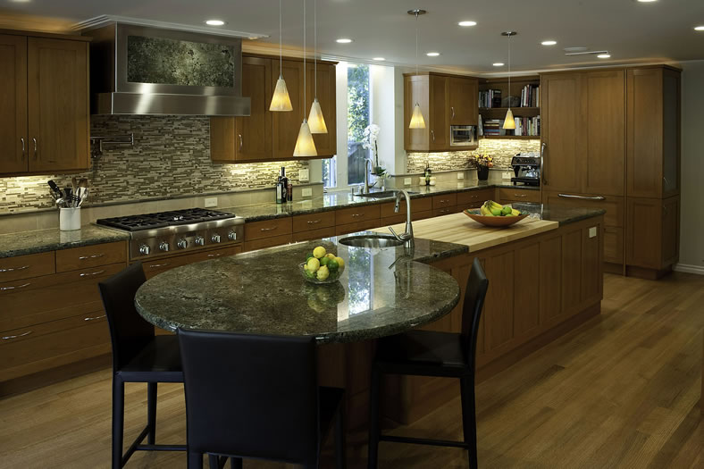 This kitchen has ample work surfaces, Including integrated butcher block prep area and seating.
