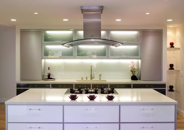 The symmetry of this kitchen is accented by the backlit glass cabinetry doors.