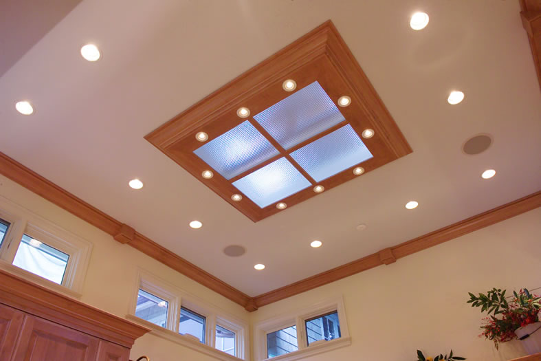 Crown molding and skylight trim match the kitchen cabinetry for a unified look.