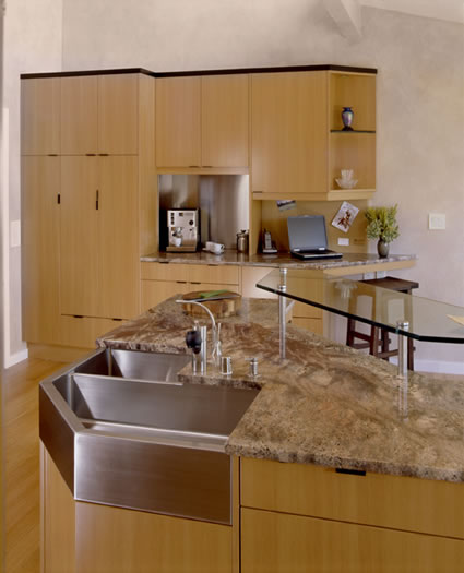 The custom 3 sided sink provides form and function for this 'L' shaped island with glass eating bar.