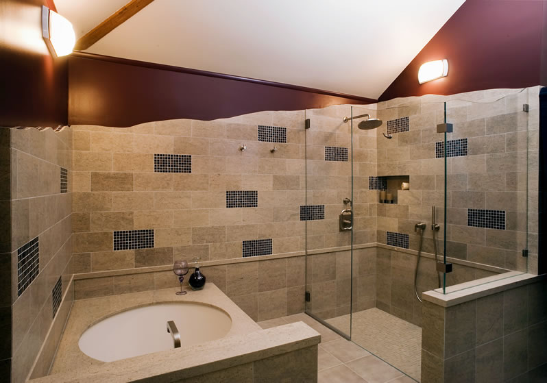 Freeform limestone tile walls flow with the custom glass enclosure.