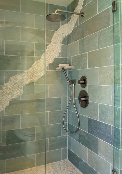 The green slate tile walls have a river of pebbles flowing through it.