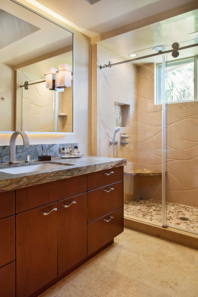 The richness of the cherry cabinetry and marble slabs gives contrast to the limestone shower and floor.