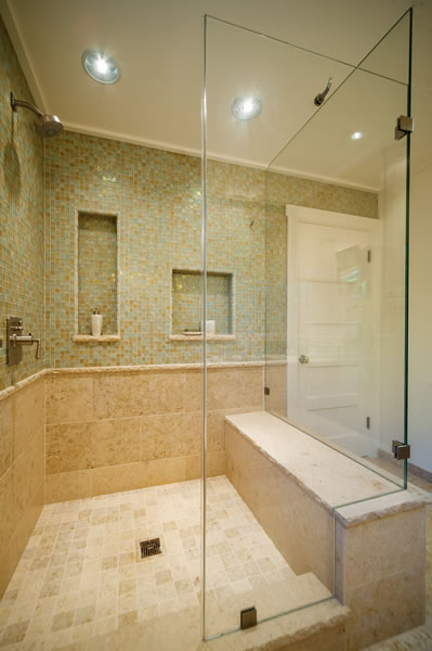 The open feel of this room is enhanced by the continuation of the shower wall tiles across the entire wall.